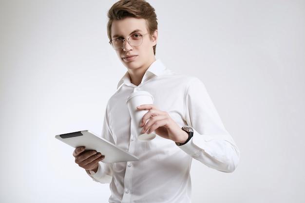 Giovane uomo d'affari sicuro in camicia con la tazza di caffè e la compressa