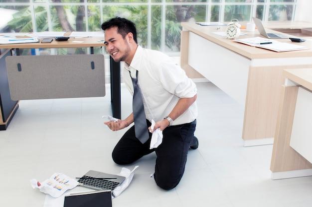 Giovane uomo d'affari sollecitato e sovraccarico di lavoro urlando in ufficio.