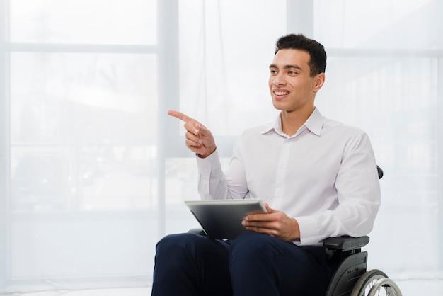 Giovane uomo d'affari sorridente che si siede sulla sedia a rotelle che giudica compressa digitale a disposizione che indica il suo dito per parteggiare