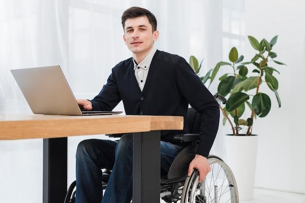 Giovane uomo d'affari sorridente che si siede sulla sedia a rotelle che per mezzo del computer portatile che esamina macchina fotografica