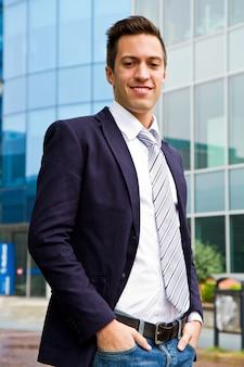 Giovane uomo d'affari sorridente che sta fuori di una costruzione