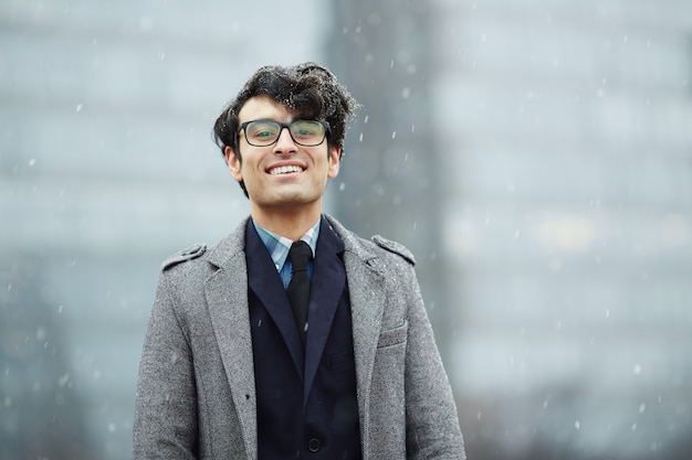 Giovane uomo d'affari sorridente in neve