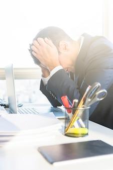 Giovane uomo d'affari stanco con il computer portatile nel suo luogo di lavoro