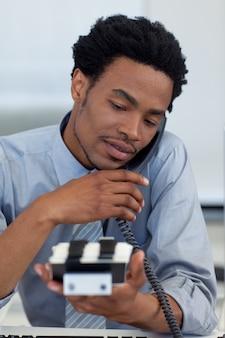 Giovane uomo d'affari sul telefono guardando titolare della carta