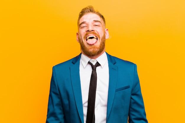 Giovane uomo d'affari testa rossa con atteggiamento allegro, spensierato, ribelle, scherzando e tirando fuori la lingua, divertendosi contro l'arancia