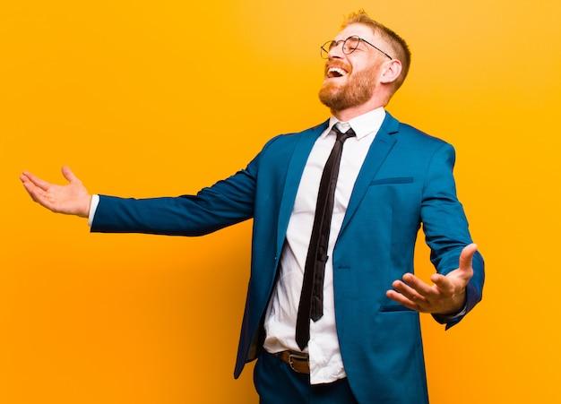 Giovane uomo d'affari testa rossa eseguendo opera o cantando in un concerto o spettacolo, sentirsi romantico, artistico e passionale