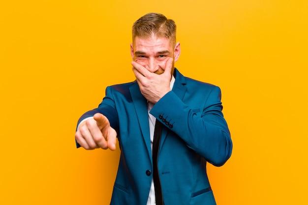 Giovane uomo d'affari testa rossa ridendo di te, indicando la fotocamera e prendendo in giro o deridendoti contro l'arancia