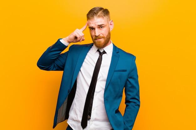 Giovane uomo d'affari testa rossa sentirsi confuso e perplesso, mostrando che sei pazzo, pazzo o fuori di testa arancione