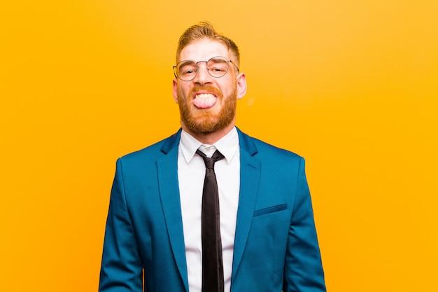 Giovane uomo d'affari testa rossa sentirsi disgustato e irritato, sporgendo la lingua, antipatia qualcosa di brutto e schifoso contro l'arancia