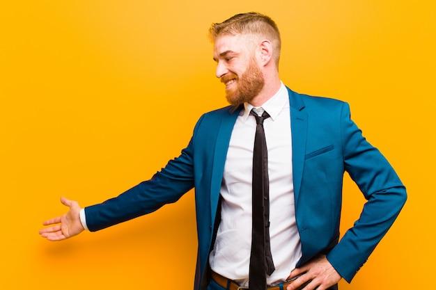 Giovane uomo d'affari testa rossa sentirsi felice e allegro, sorridente e darti il benvenuto, invitandoti a entrare con un gesto amichevole contro l'arancia
