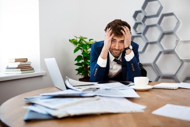 Giovane uomo d'affari turbato che si siede nel luogo di lavoro, fondo dell'ufficio.