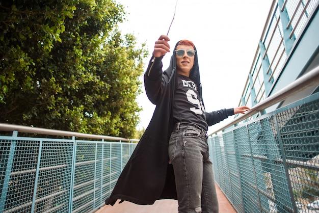 Giovane uomo da portare alla moda che gira intorno su un ponte