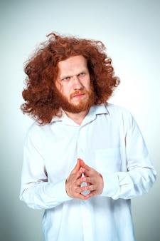 Giovane uomo dai capelli rossi che osserva da parte