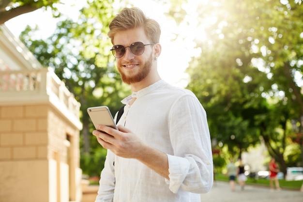 Giovane uomo dai capelli rossi positivo e sorridente con la barba e l'orecchino in occhiali da sole che guardano attraverso i social network sul suo smartphone sulla strada di casa.
