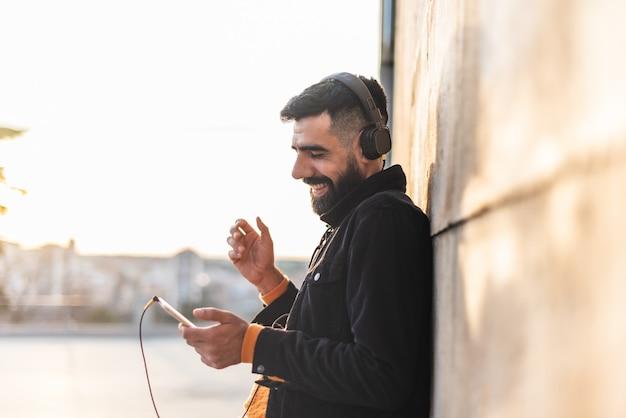 Giovane uomo dei pantaloni a vita bassa che per mezzo del telefono cellulare e della musica d'ascolto.