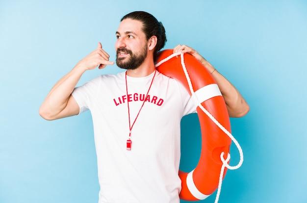 Giovane uomo del bagnino che tiene un galleggiante di salvataggio che mostra un gesto di chiamata di telefono cellulare con le dita.