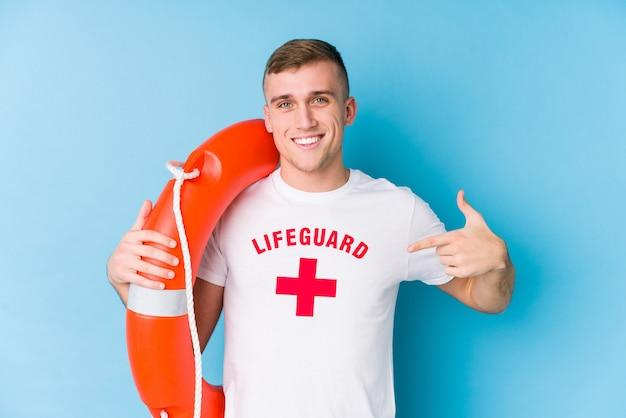 Giovane uomo del bagnino che tiene una persona del galleggiante di salvataggio che indica a mano uno spazio della copia della camicia, fiero e sicuro