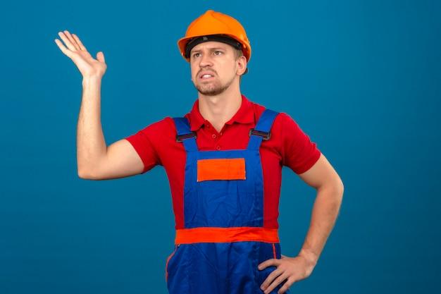 Giovane uomo del costruttore in uniforme della costruzione e casco di sicurezza che cercano facendo gesto confuso con la mano e l'espressione come fare domanda sopra la parete blu isolata