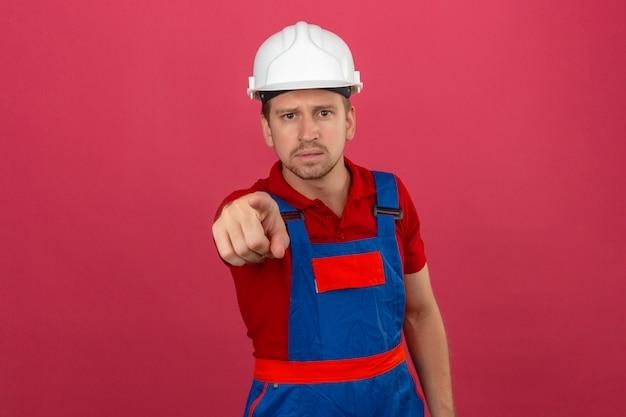 Giovane uomo del costruttore in uniforme della costruzione e casco di sicurezza che indica il dito indice verso la macchina fotografica e l'espressione come fare domanda sopra la parete rosa isolata