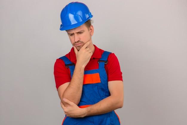 Giovane uomo del costruttore in uniforme della costruzione e casco di sicurezza che pensa e che tocca il suo sguardo confuso mento che ha dubbi sopra la parete bianca isolata