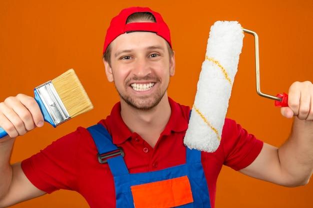 Giovane uomo del costruttore in uniforme e costruzione dello spiritello malevolo rullo di pittura e spazzola della tenuta con il grande sorriso sul fronte sopra la parete arancio isolata
