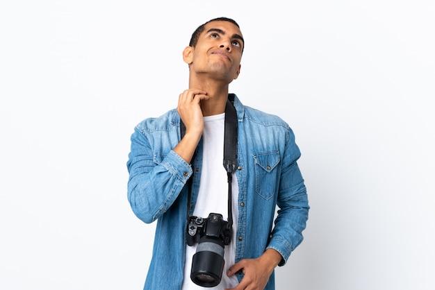 Giovane uomo del fotografo afroamericano sopra la parete bianca isolata che pensa un'idea