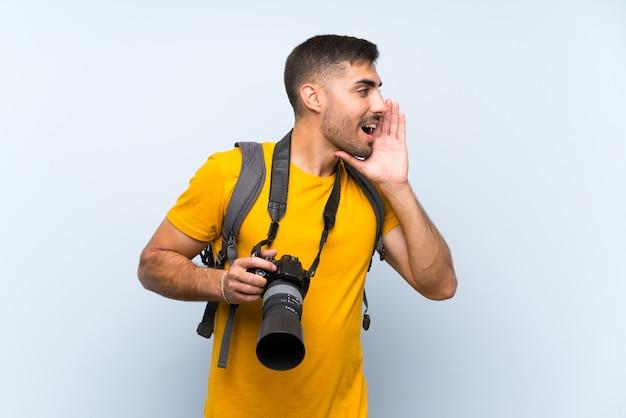 Giovane uomo del fotografo che grida con la bocca spalancata