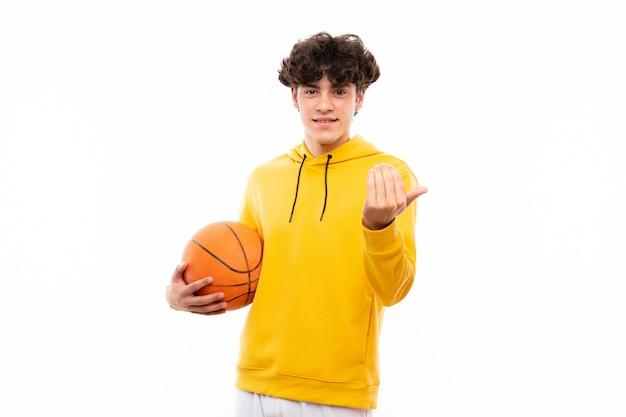 Giovane uomo del giocatore di pallacanestro sopra la parete bianca isolata che invita a venire con la mano. felice che tu sia venuto