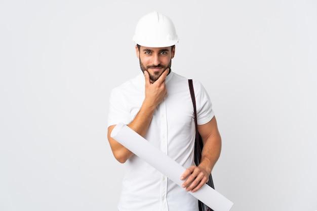 Giovane uomo dell'architetto con il casco e giudicare i modelli isolati sul pensiero bianco della parete