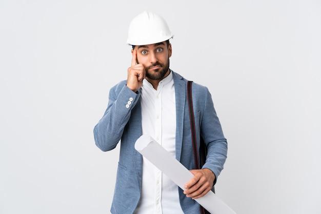 Giovane uomo dell'architetto con il casco e giudicare i modelli isolati sulla parete bianca che pensa un'idea