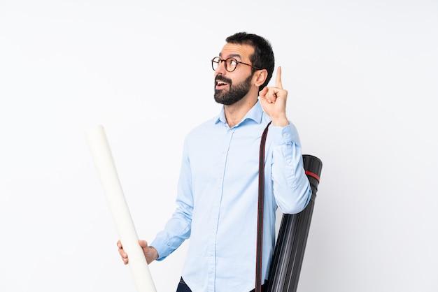 Giovane uomo dell'architetto con la barba sopra fondo bianco isolato che pensa un'idea che indica il dito su
