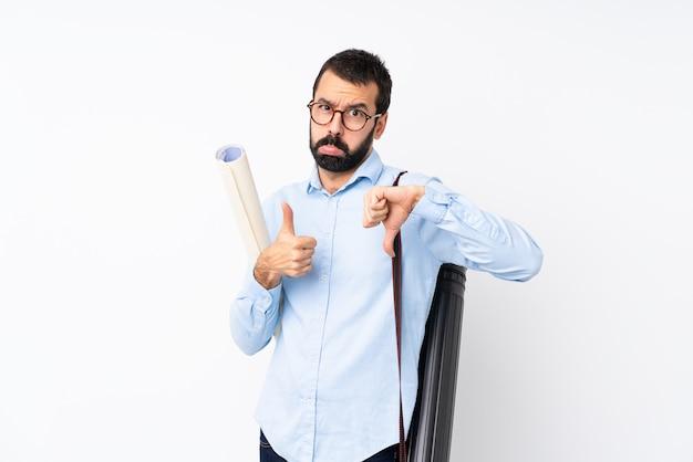 Giovane uomo dell'architetto con la barba sopra la parete bianca isolata che fa buon cattivo segno. indeciso tra sì o no