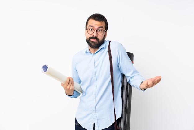 Giovane uomo dell'architetto con la barba sopra la parete bianca isolata che fa gesto di dubbi