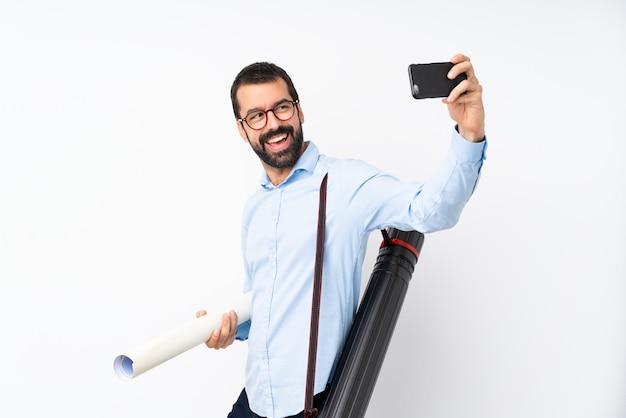 Giovane uomo dell'architetto con la barba sopra la parete bianca isolata che fa un selfie