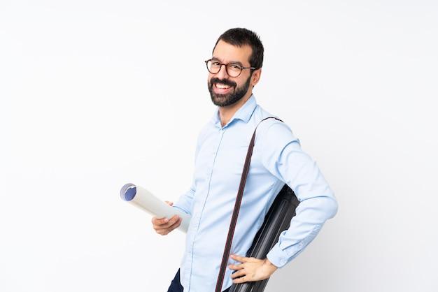 Giovane uomo dell'architetto con la barba sopra la parete bianca isolata con i vetri e sorridere