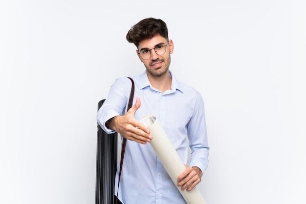 Giovane uomo dell'architetto sopra stretta di mano bianca isolata dopo il buon affare
