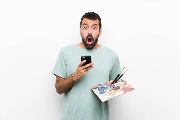 Giovane uomo dell'artista che giudica sorpreso e che invia un messaggio una tavolozza sopra la parete isolata