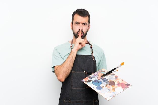 Giovane uomo dell'artista che tiene una tavolozza che mostra un segno di gesto di silenzio che mette il dito in bocca