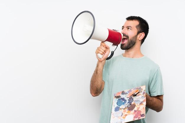 Giovane uomo dell'artista che tiene una tavolozza sopra la parete isolata che grida tramite un megafono