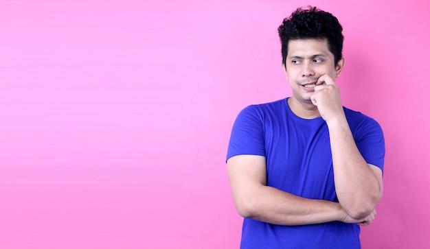 Giovane uomo dell'asia del ritratto che ha dubbi e con l'espressione confusa del fronte su fondo rosa in studio