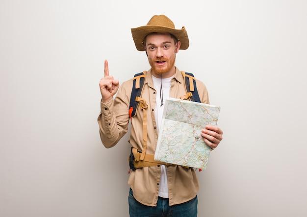 Giovane uomo dell'esploratore di redhead che ha una grande idea, concetto di creatività. in possesso di una mappa.