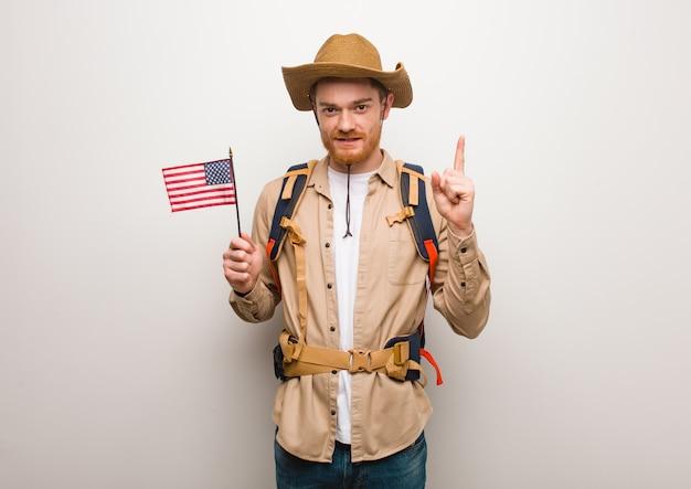 Giovane uomo dell'esploratore di redhead che mostra numero uno. in possesso di una bandiera degli stati uniti.