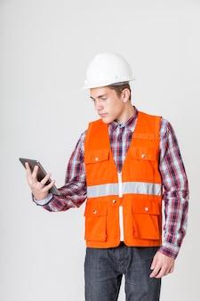 Giovane uomo dell'ingegnere che per mezzo dello smartphone su fondo bianco.