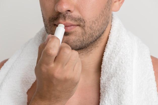 Giovane uomo della stoppia con l'asciugamano bianco che applica balsamo sulle labbra