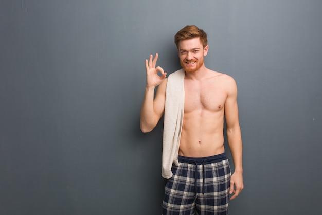 Giovane uomo della testarossa che tiene un asciugamano allegro e sicuro facendo gesto giusto. sta tenendo un asciugamano bianco.