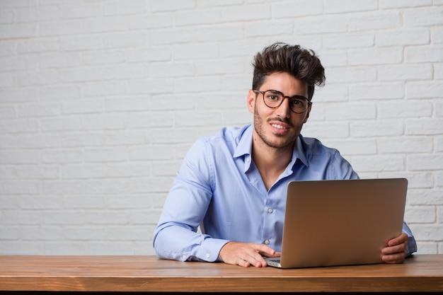 Giovane uomo di affari che si siede e che lavora ad un computer portatile allegro e con un grande sorriso, sicuro, amichevole e sincero, esprimente positività e successo