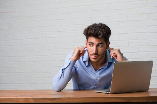 Giovane uomo di affari che si siede e che lavora ad un computer portatile che copre le orecchie di mani, arrabbiato e stanco di sentire del suono