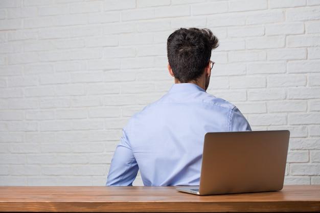 Giovane uomo di affari che si siede e che lavora ad un computer portatile che mostra indietro, posante ed aspettante, guardante indietro