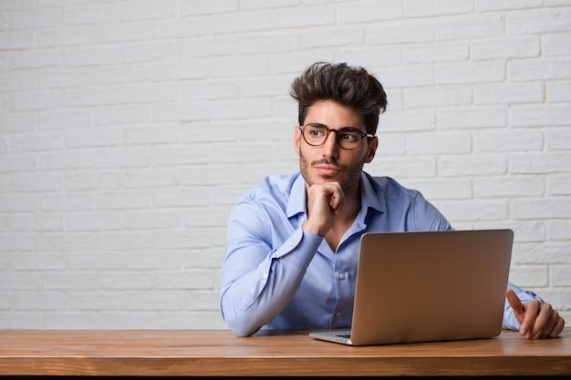 Giovane uomo di affari che si siede e che lavora ad un computer portatile che pensa e che osserva in su