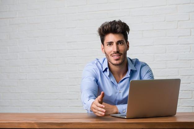 Giovane uomo di affari che si siede e che lavora ad un laptop che raggiunge fuori per accogliere qualcuno o che gesturing per aiutare, felice ed eccitato